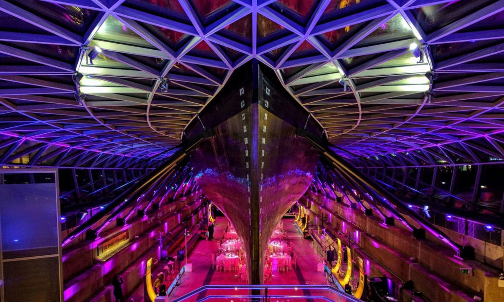 A photo of under the hull of the cutty sark. The image shows the hull and the event Space below which has cabaret tables set up on it. The Space is lit up with purple and pink lighting.