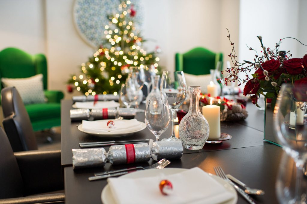 A private dining venue perfect for your office Christmas party. A close-up shot of the dining table at the Ampersand, the table is set for dinner with Christmas crackers. There is a Christmas tree in the background.