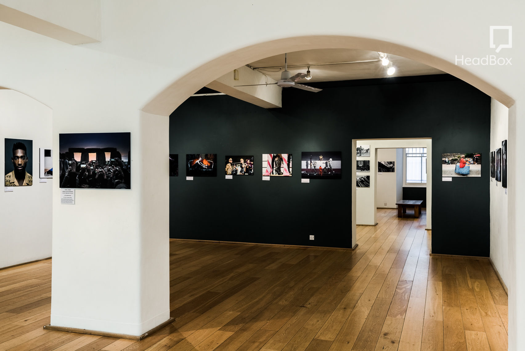 A art gallery with a curved arch and white and black walls