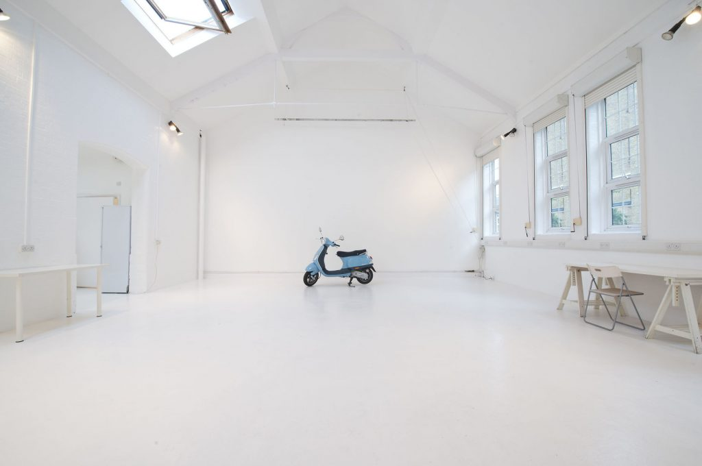 open white studio with blue motorbike one of Londons unique photography studios