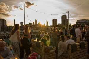 rooftop bar at dusk with groups of people networking and sitting on wooden seats