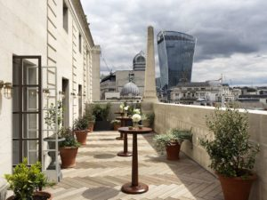 rooftop terrace with potted plants and high tables overlooking central london