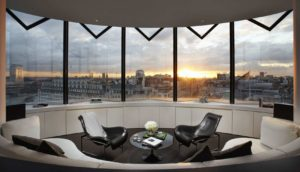 penthouse suite with wide windows overlooking london and plush seating