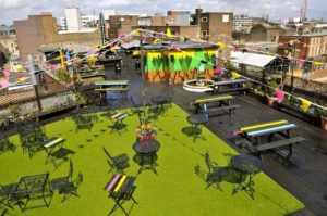 rooftop terrace with fake grass, picnic benches, chairs and tables