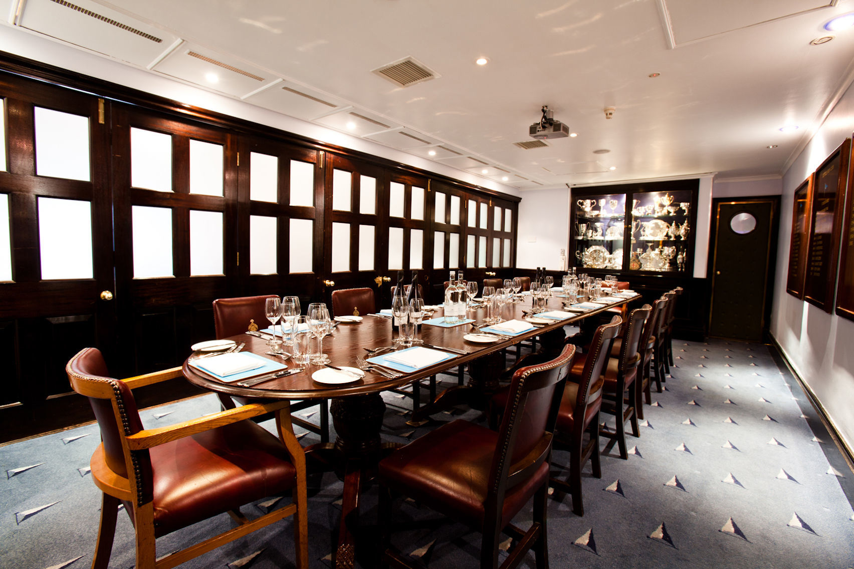 A private dining room with a dark wooden table and wood paneling on the walls