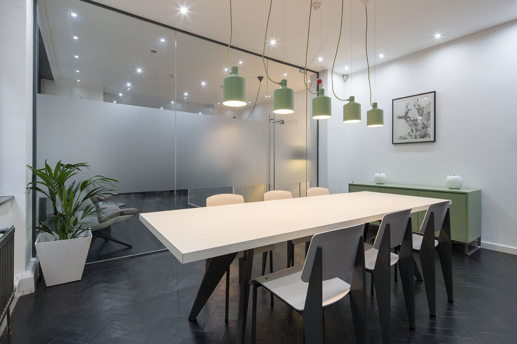 A white meeting room with a glass wall and green furnishings