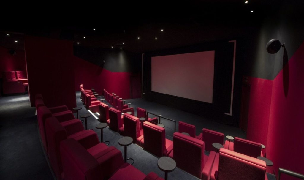 screening room with red seating and red walls.