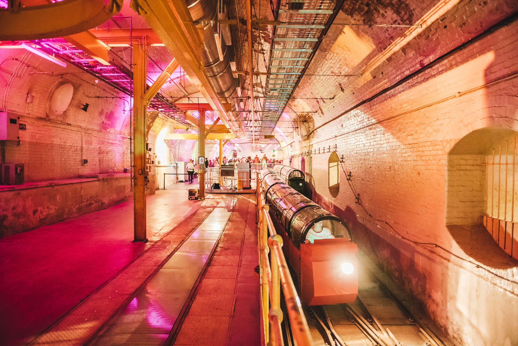An unusual party venue London, the mail rail is an underground industrial venue with exposed pipes, bricks and archways. The venue is lit up with pink and orange lightening and the mail rail takes pride of place on the right hand side.