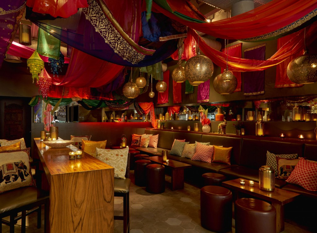 Anise Bar, Cinnamon Kitchen is a party venue in London, the room is atmospheric with lots of bright decor covering the ceiling. There are circular light hanging from the ceiling and the banquette seating has lots of brightly coloured cushions spread across it.
