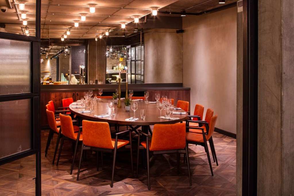 A small private dining room with a oval oak table and orange chairs arranged around it. There are bright lightbulbs on the ceiling and a bar in the background.