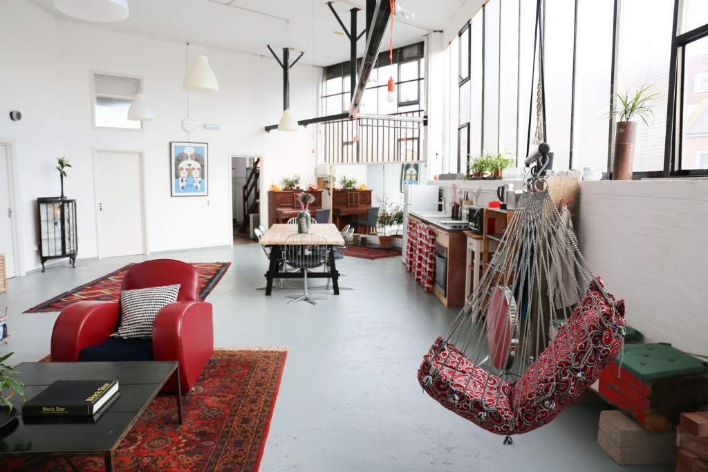 A stylish space with white walls, large windows along one side and furniture including armchairs, tables and chairs.