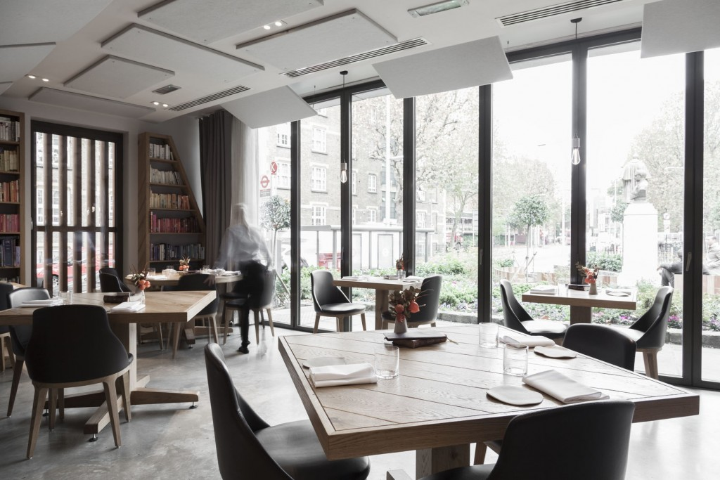 Bright fancy restaurant with floor to ceiling windows looking out onto gardens. Five square wooden tables are arranged in the Space with two black chairs tucked under each table. Shelves along the back wall are filled with old looking books.