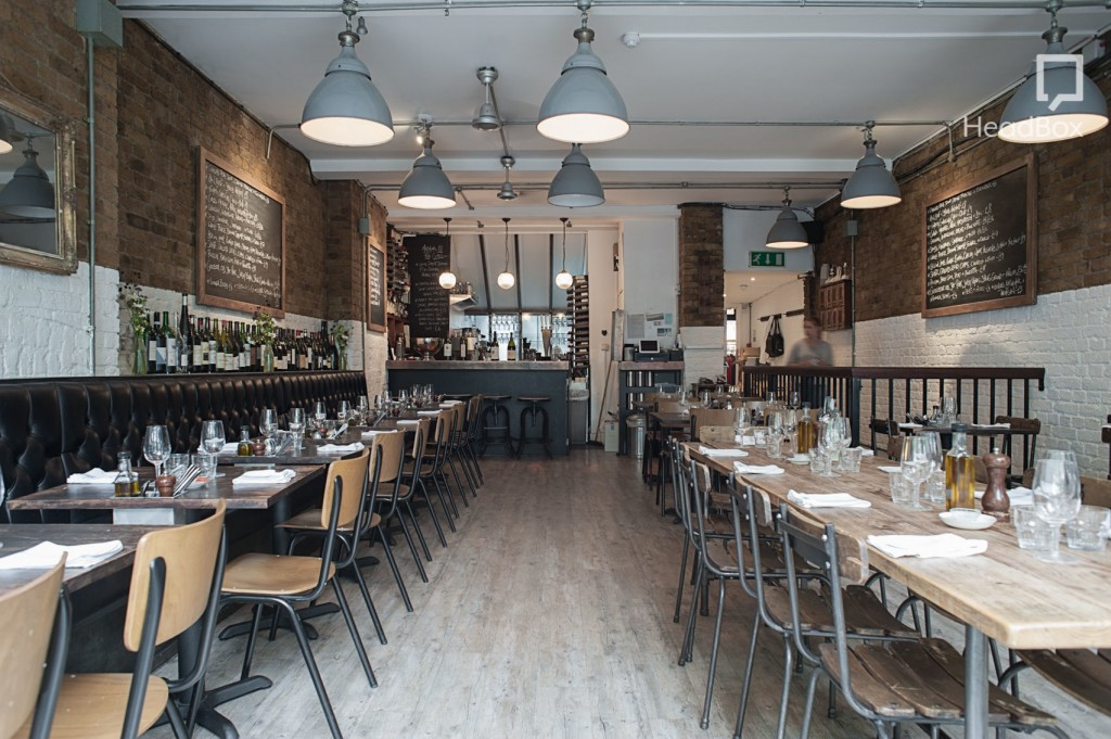 8 Hoxton Square restaurant. A long room with partially exposed brick walls, grey lamps hanging from the ceiling and wooden tables and chairs running the length of both sides. A grey bar sits at the far end of the room.