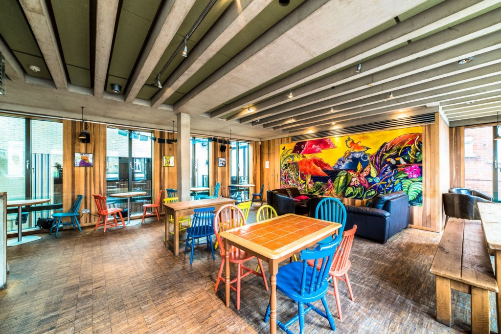 A large restaurant with several orange tables and brightly coloured chairs placed around them. On the back wall there is a large art piece with bright coloured graffiti style pattern.