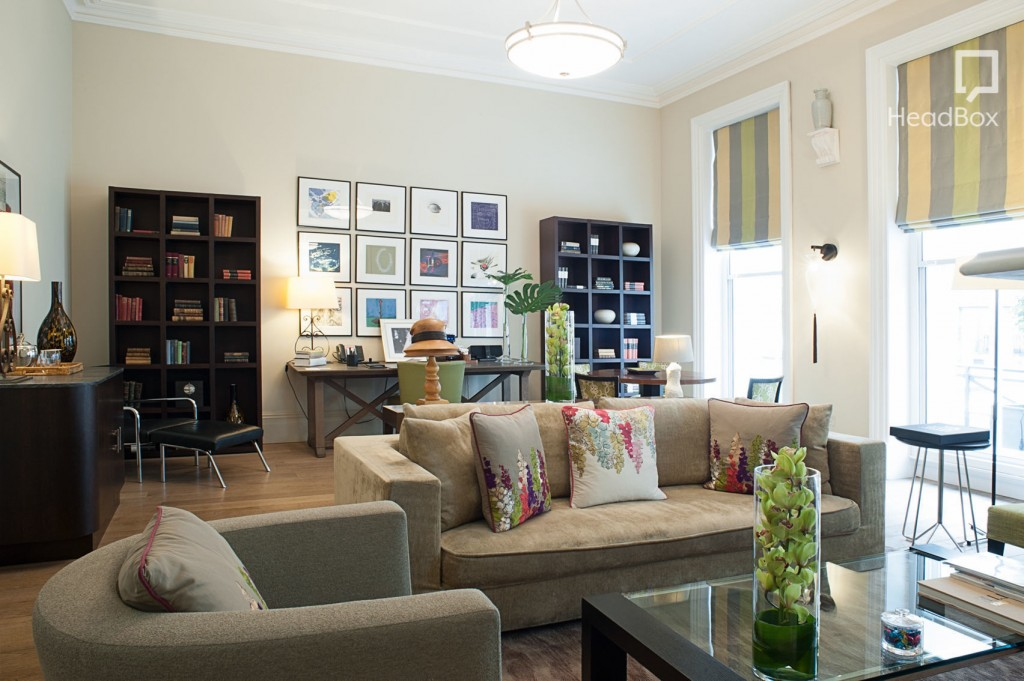 A comfortable room with large windows, framed pictures and bookshelves, a desk and a sofa and armchair around a coffee table.