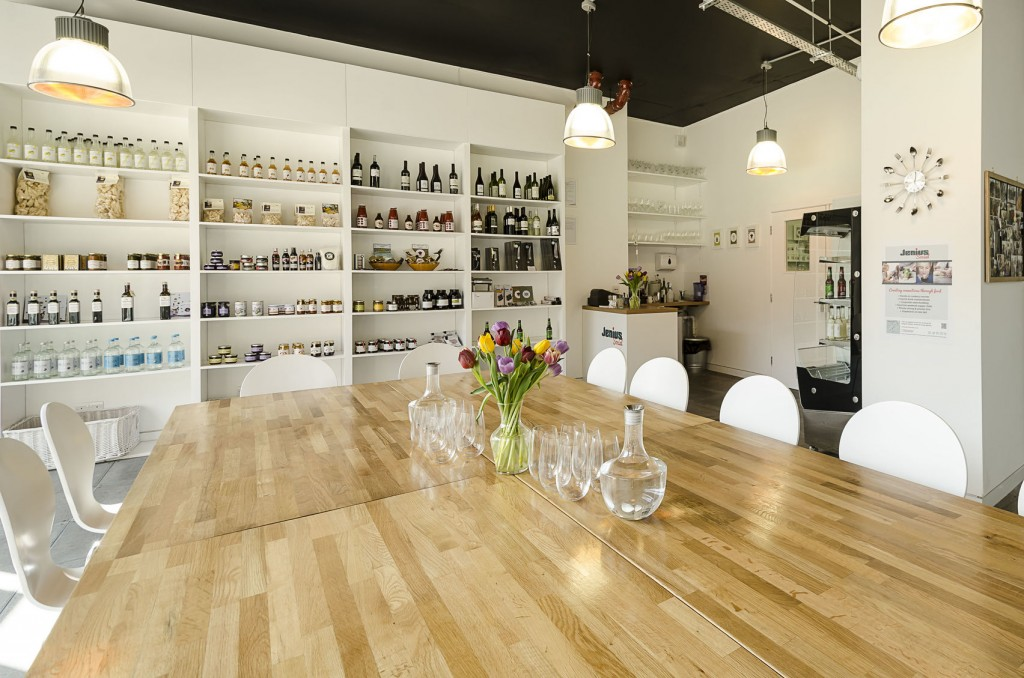 A large white room with shelves in the background with lots of bottles of wine and spirits. In the foreground theres a large oak table with white chairs around it.