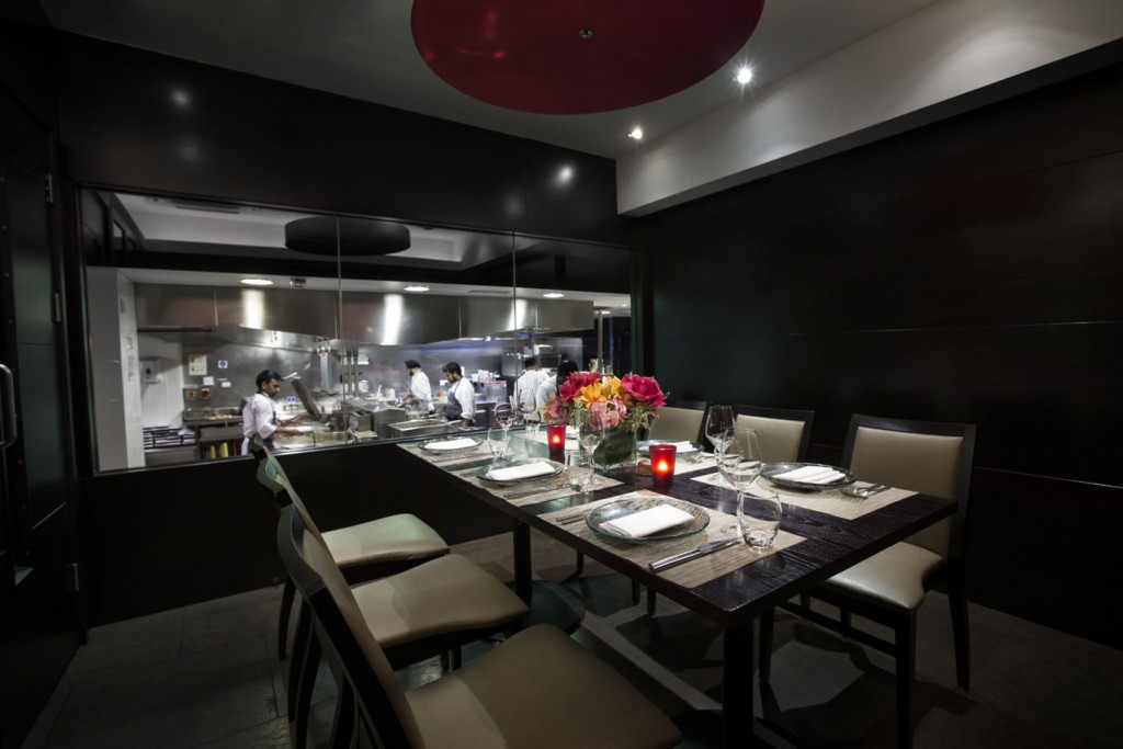 Chef's Table at Benares Restaurant, dark room with black walls and a window looking into a restaurant kitchen. A dining table sits in the centre laid for supper with two candles and a bunch of flowers in the centre. Six light grey chairs sit around the table.