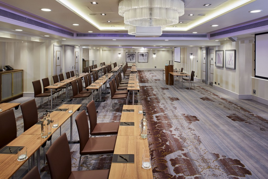 A large meeting room with pictures on the walls, projector screens and several long tables with chairs set out.