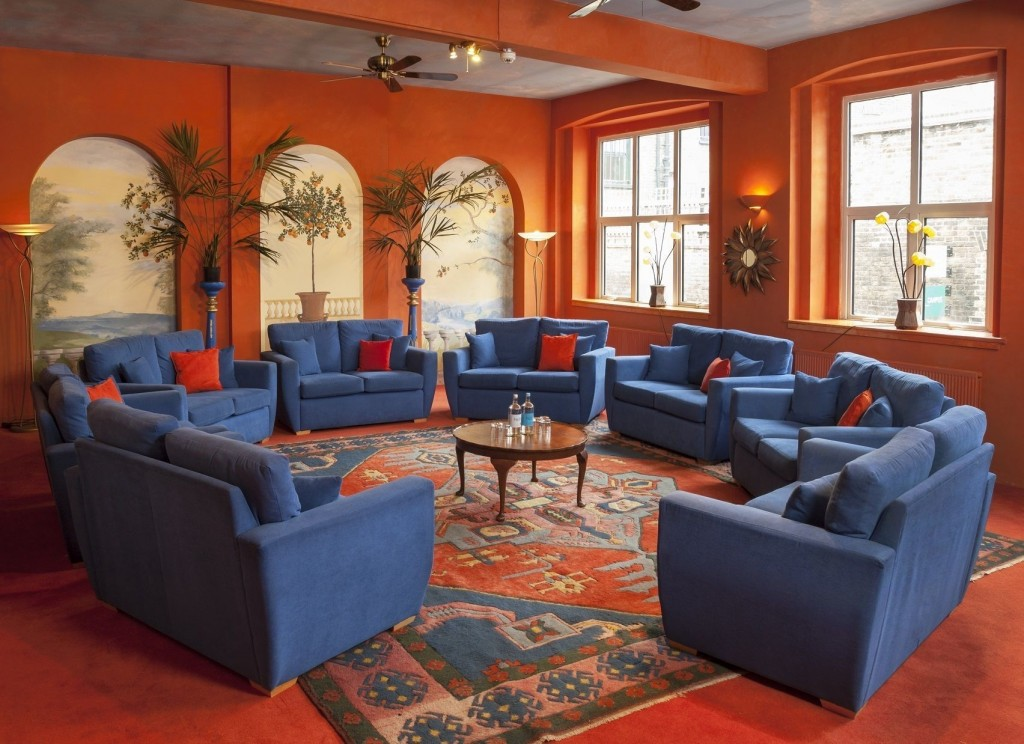 bright orange room with blue sofas