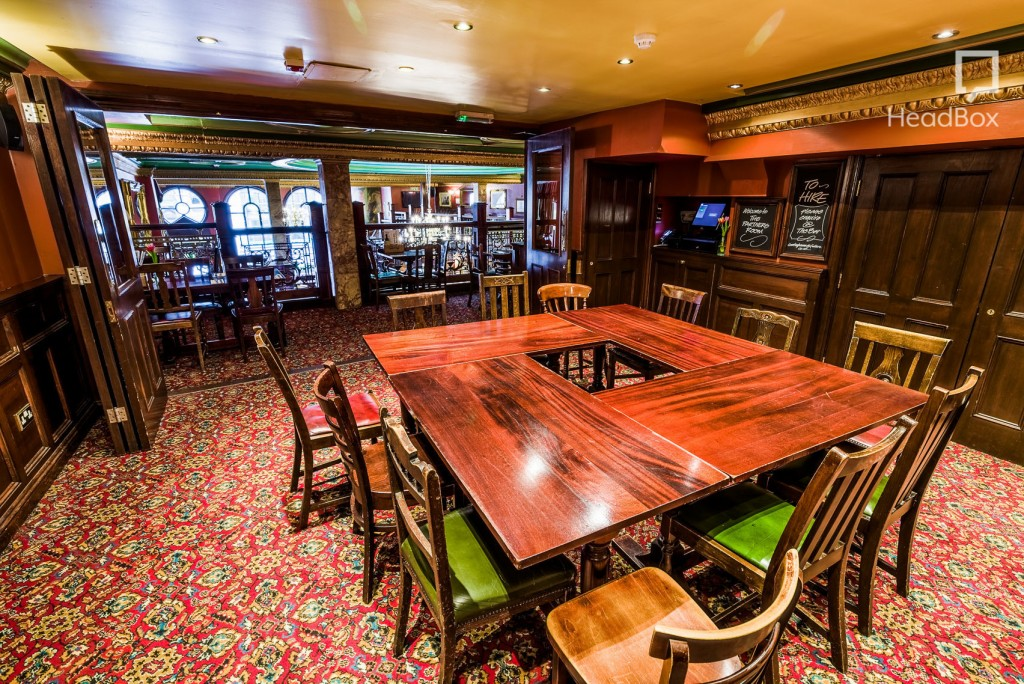 A private room in a pub with coloured carpet and one square table that is surrounded by dark wood chairs.