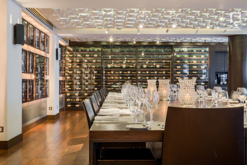 Luxury restaurant at the Andaz Hotel in london. Large square wooden private dining table with sleek brown leather chairs tucked in around it is laid for a meal. The room is bright with a white, textured ceiling and fully stocked wine racks shielded with glass line the walls.