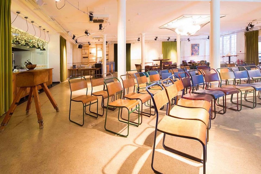 A large training room with several pillars and rows of wooden chairs set out in a horseshoe shape.
