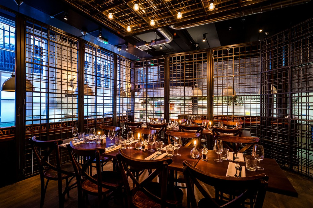 A Private Dining Room Surrounded By Caged Metal Slates. There Are Two Dark  Brown Tables Part 83