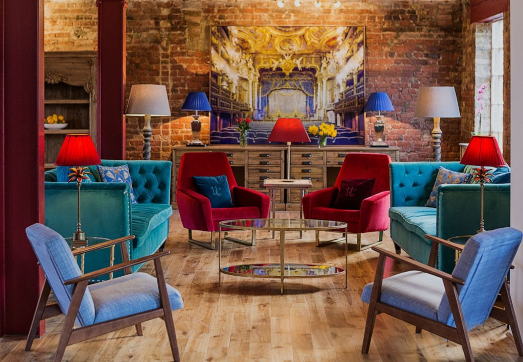 A room with exposed brick walls, a large mirror on one wall and several stylish jewel coloured chairs, sofas and lamps.