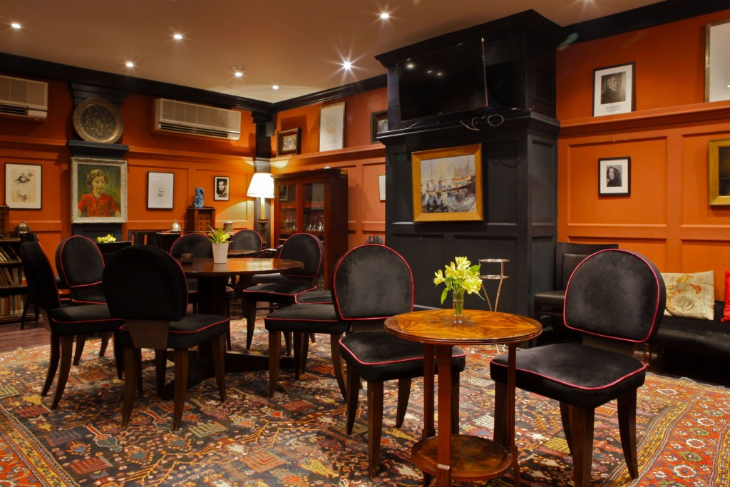 A Private Dining Room With Small Circular Tables And Black Chairs. The  Walls Are Orange Part 88