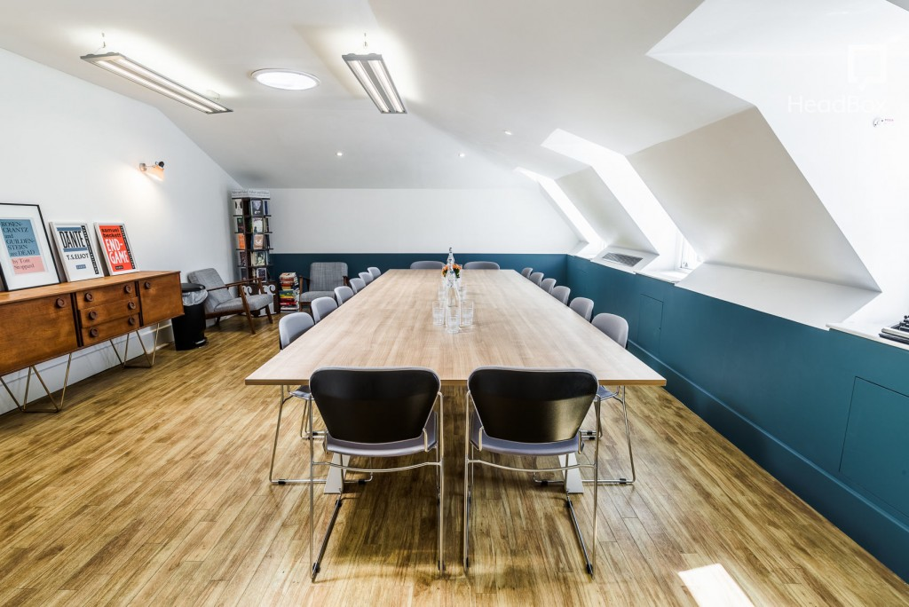 A bright meeting room with sloping wall, wooden floors, posters and modern furniture.