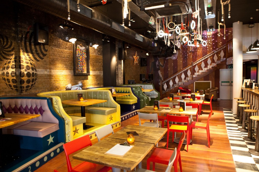 A room with high ceilings, brightly coloured seating booths, tables and chairs and decorations hanging from the ceiling.