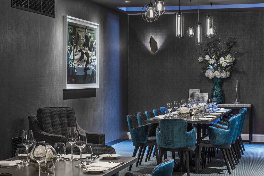 fancy private dining room at M Restaurant: dark grey room with large framed picture mounted on the wall, two long grey dining tables laid for dining and surrounded by blue velvet plush chairs. A tall bouquet of white and blue flowers in a blue vase sits on a table at the end of the room.