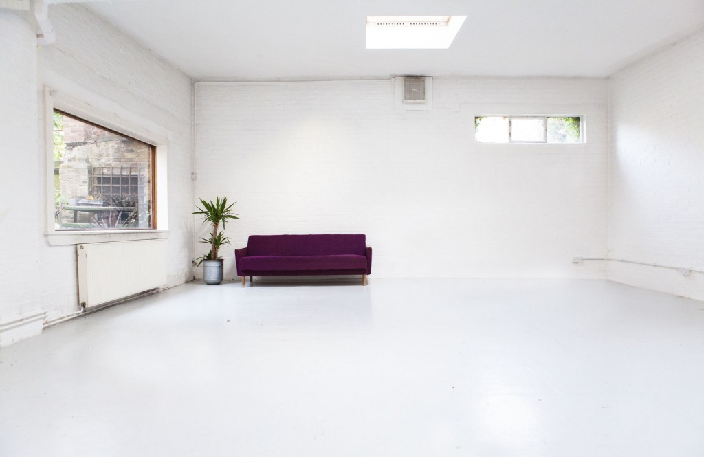 A training room with white floor, ceiling and walls, a large window on one wall, small windows on the back wall and a purple sofa in the corner.