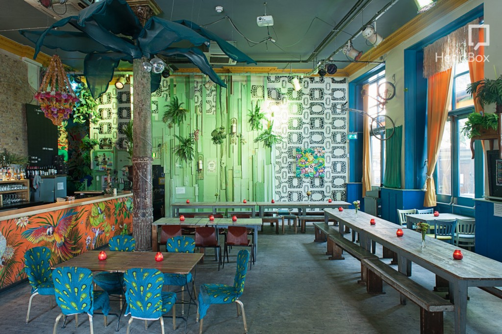 A quirky restaurant space decorated with brightly coloured patterned walls.