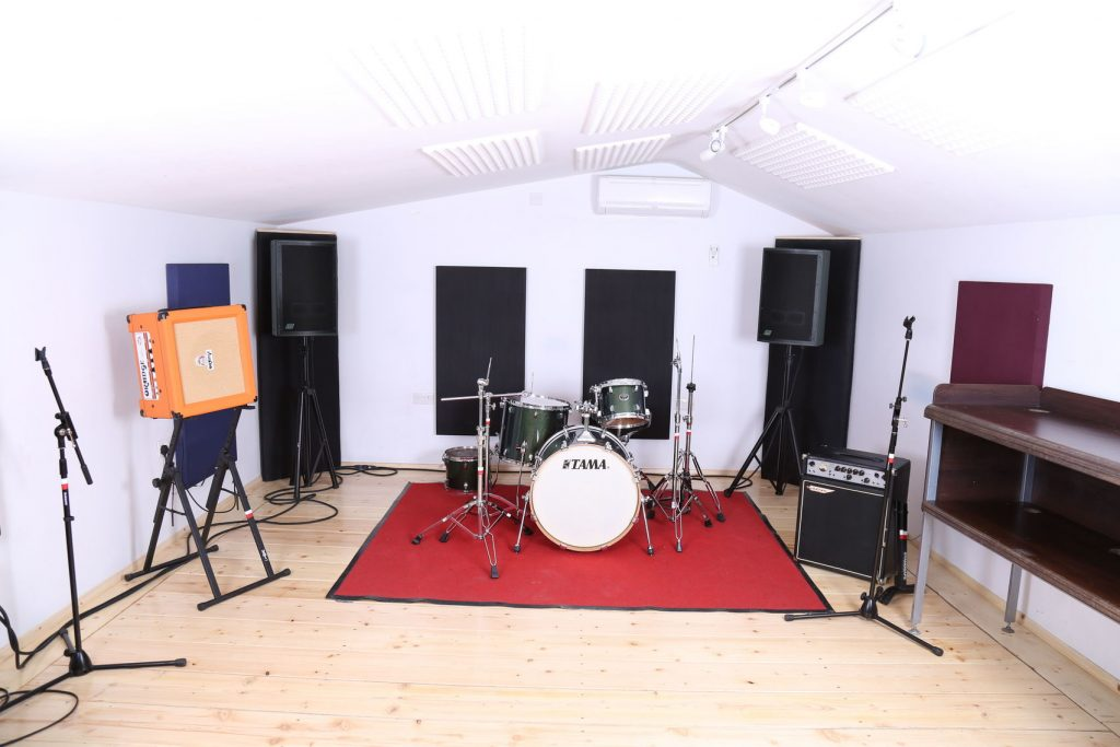 a large white studio with a pale wooden floor is filled with large speakers, a drum kit which is placed on top of a red carpet and a microphone stand.