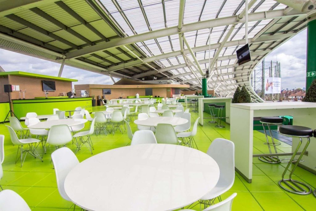 roof terrace with green flooring, white tables and chairs, overlooking a cricket ground