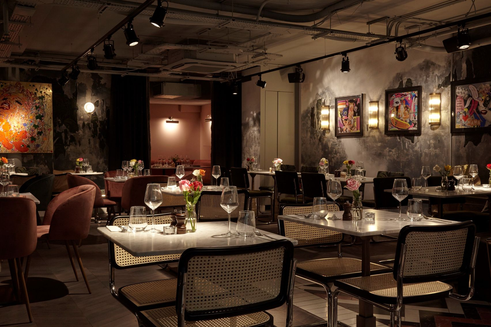 A large private dining room with white marble tables and art on the walls