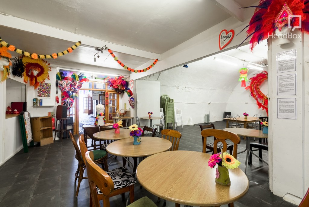 A space with an arched ceiling, white walls, brightly coloured decorations and several tables and chairs.