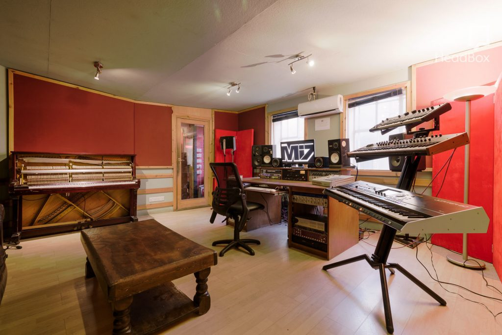 a red studio space has a grand piano placed in one of the corners and a 3 tiered keyboard in the other. There is a brown coffee table in the centre of the room as well as a desk with lots of mixing desks and a desk chair pushed up against it.
