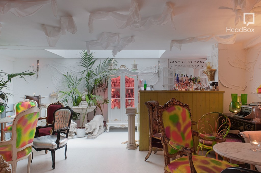 A large white room full of quirky decor, including a large plant, a white cabinet and neon printed armchairs