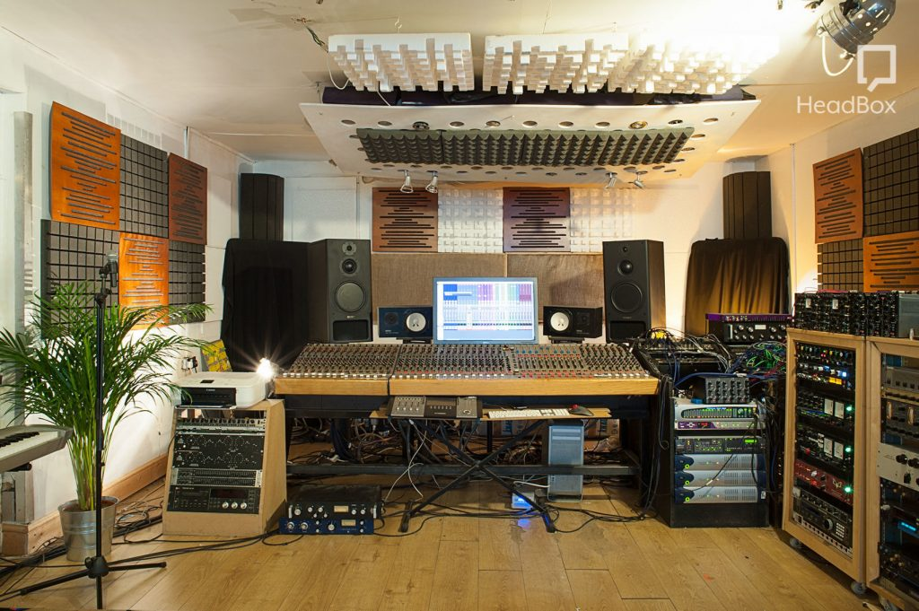 a modern and urban recording studio has a large desk with mixers and a HD screen. There are two large speakers standing on the corners of the desk and the walls are covered in song lyrics and aztec printings.