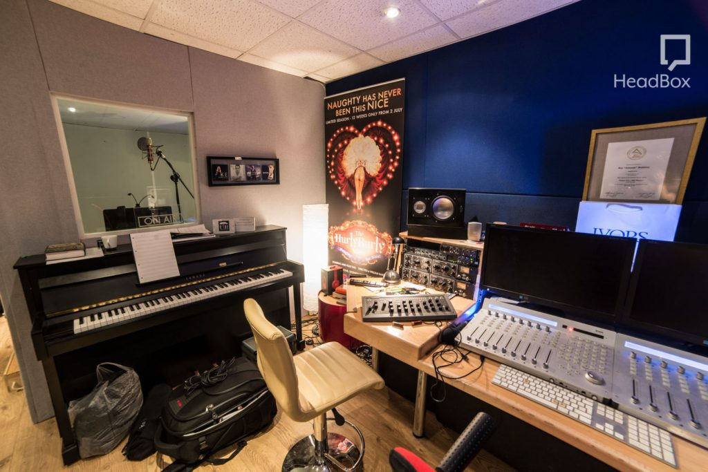 a grand piano sits in a busy recording studio, next to the piano is a desk with a mixing desk and other technology used to record music. There is a glass window on the wall which looks into a recording booth with a tall standing microphone.
