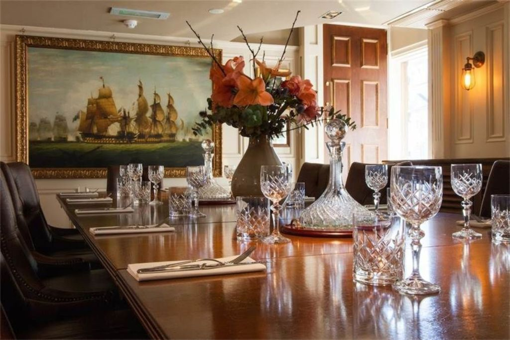 a large brown private dining table is in the foreground of the shot. There is crystal glassware set up on the table as well as a large vase with orange flowers in it. There is a large framed painting on the back wall of a large ship sailing.