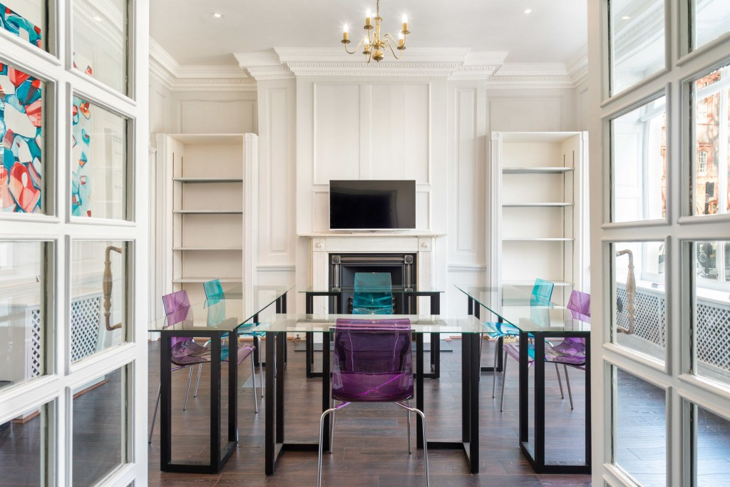 Bright and airy meeting room with four glass tables arranged into a square in the centre of the room/ Purple and blue perspex chairs are tucked under the tables. There is a wide screen TV mounted above a fireplace along the back wall.