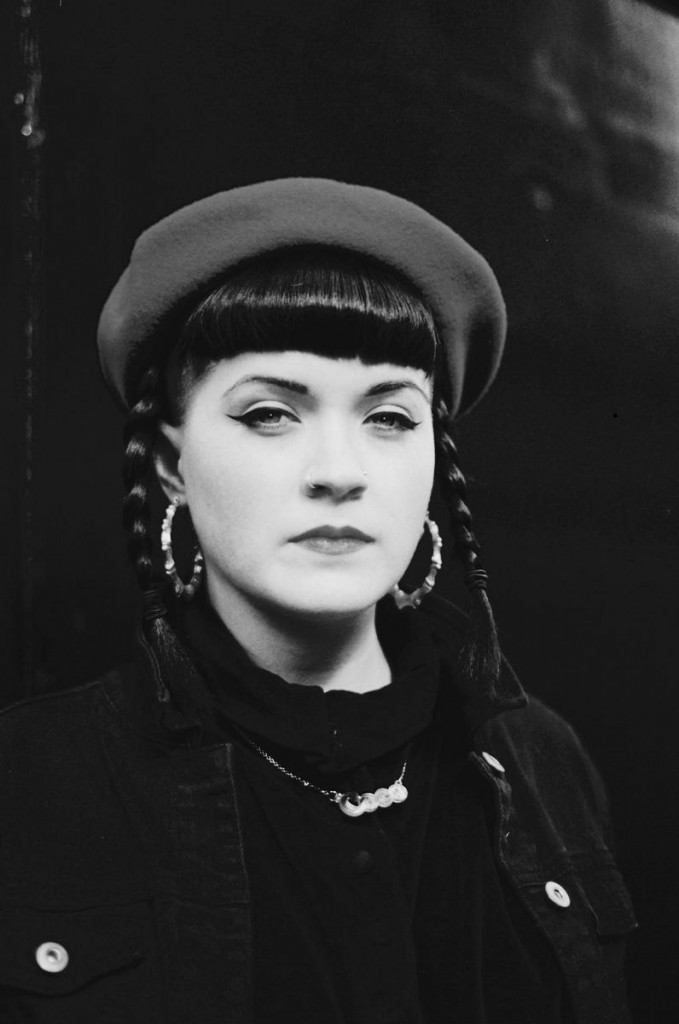 a black and white photo of coco cole staring at the camera. She has a short fringe, two plaits, large hoop earrings and is wearing a beret