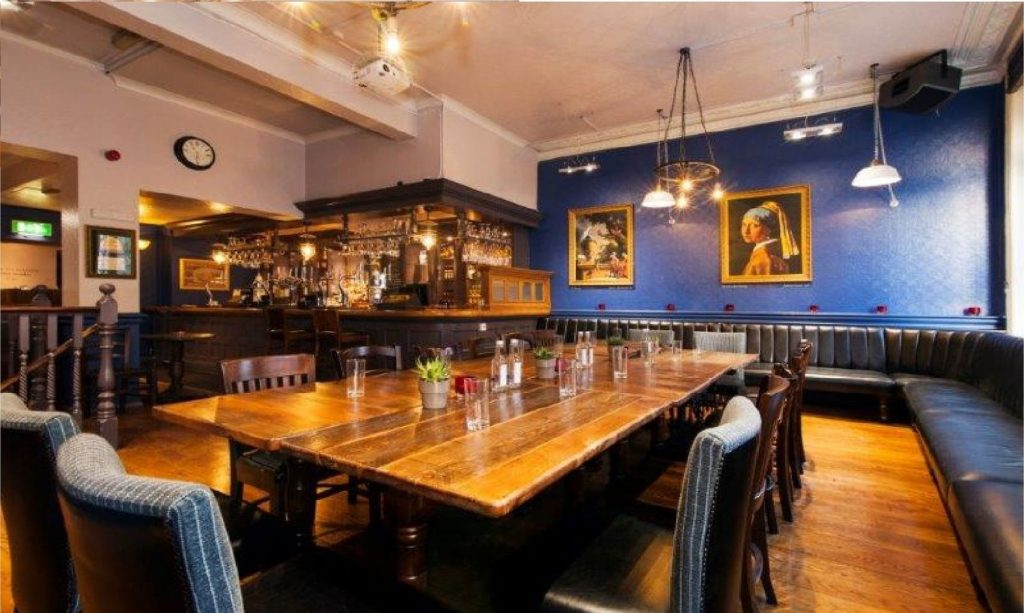 a large pub has a wooden table in the centre of a mezzanine level space. the walls of this space are royal blue and there is a photo a woman hanging on the back wall.