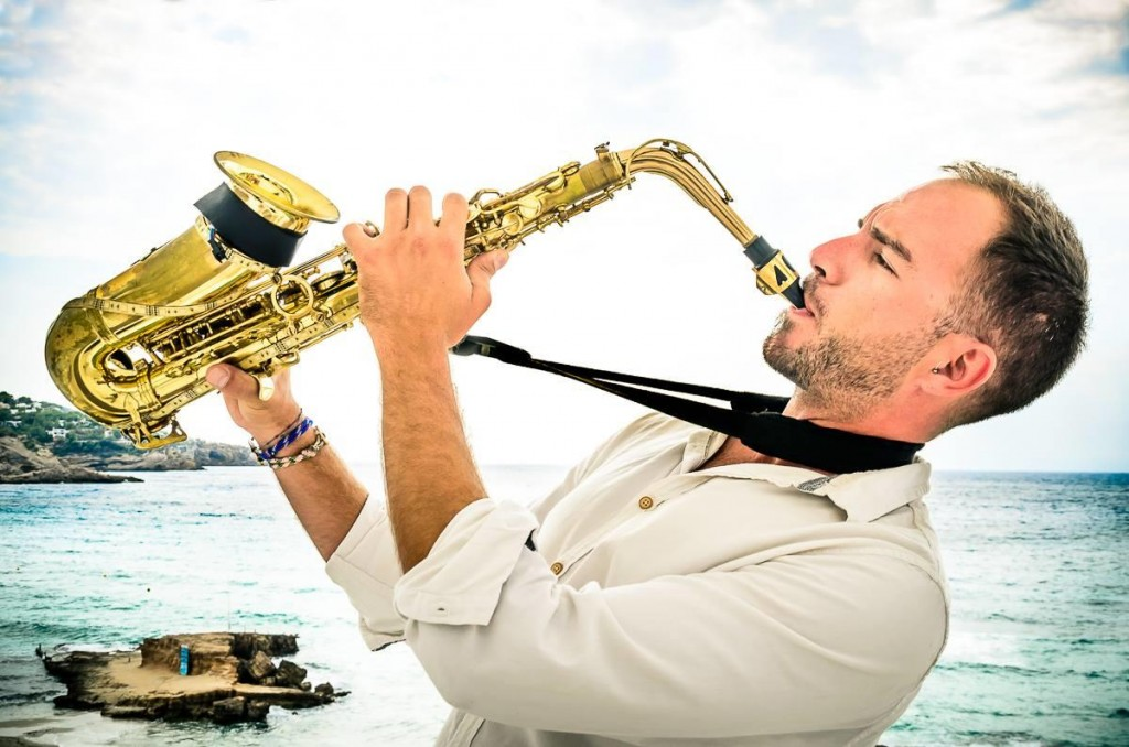 man in white playing saxophone