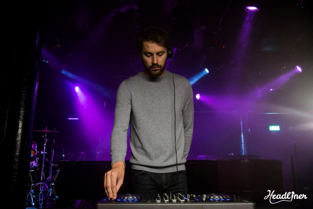 brown haired man wearing headphones and a grey jumper stands over DJ decks with purple and blue spotlights in the background