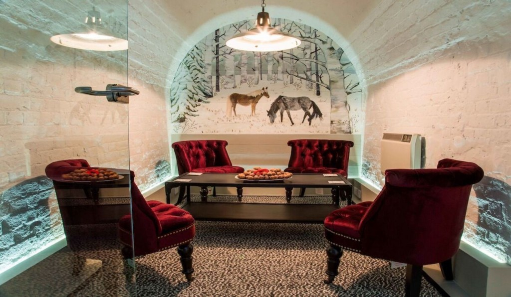 Quirky meeting room with four red velvet chairs arranged around a low brown coffee table. There is a mural of grazing horses in a snowy setting on the back wall