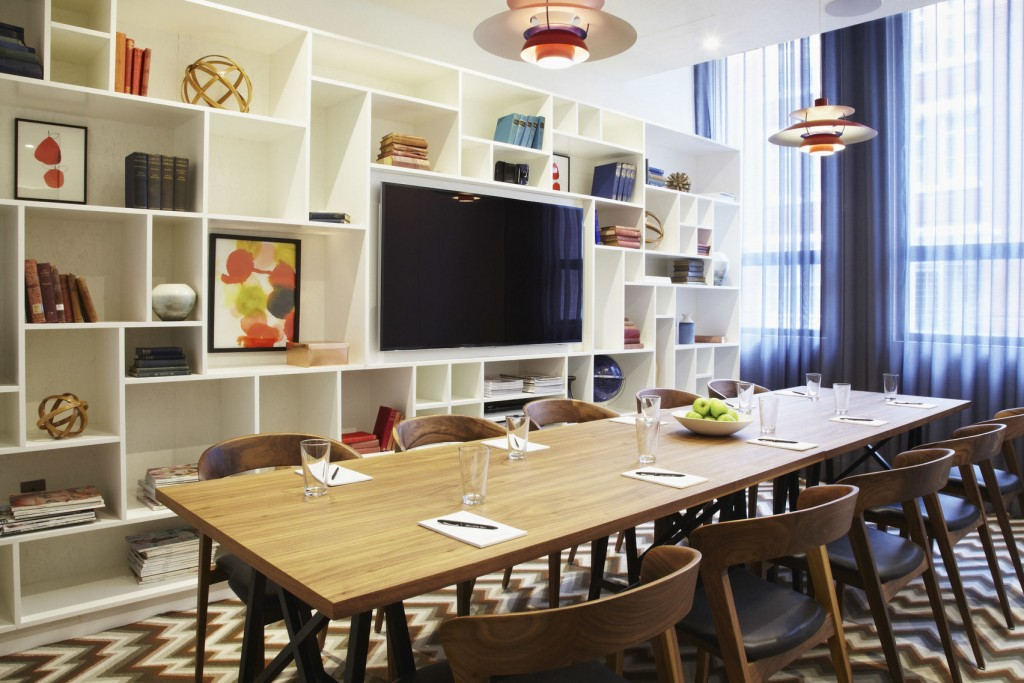 a room with a white block shelving unit housing colourful books and artwork and a Wide screen TV. A long meeting table surrounded by chairs and laid it water glasses and note pads sits in front of the shelves